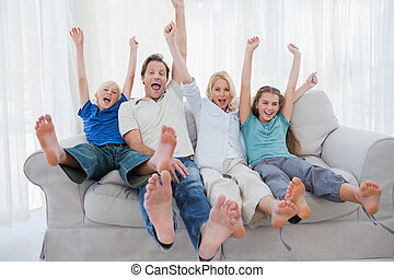 Family sitting on a couch and raising arms