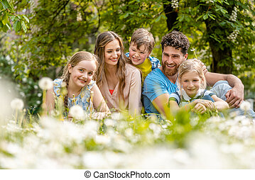 Family sitting on a meadow in summer or spring
