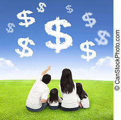 family sitting on a meadow with money of clouds in the blue...