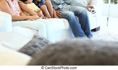 Family sitting on a sofa while look