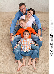 family sitting on a white carpet