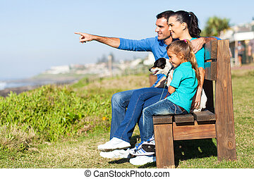 family sitting on beach bench