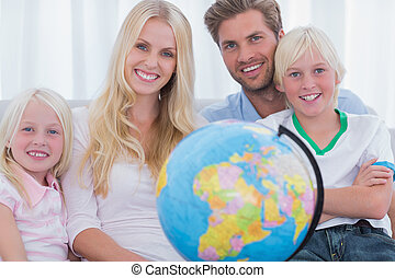 Family sitting on couch holding globe