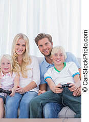 Family sitting on couch playing video games