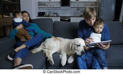 Family sitting on couch with pet labrador at home