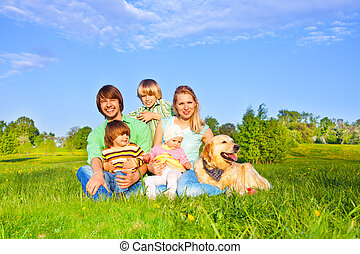 Family sitting on green grass with dog