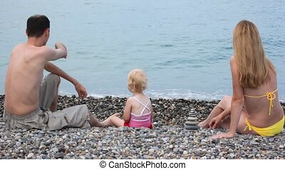 family sitting on pebble beach and throwing stones in sea