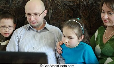 Family sitting on sofa and stares at laptop screen