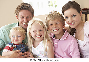 Family Sitting On Sofa At Home Together