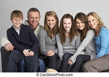 Family Sitting On Sofa