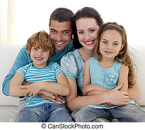 Family sitting on sofa together - Family in living-room...