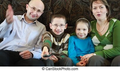 Family sitting on the couch and pass each other remote control