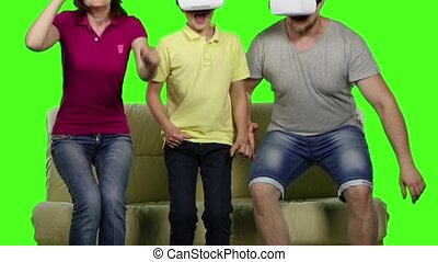 Family sitting on the sofa with glasses of virtual reality. Green screen. Slow motion