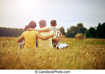 Family sitting on wheat field in sunny day