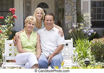 Family Sitting Outside House