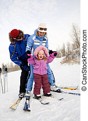 Photo of Caucasian family fond of skiing on mountainside in winter