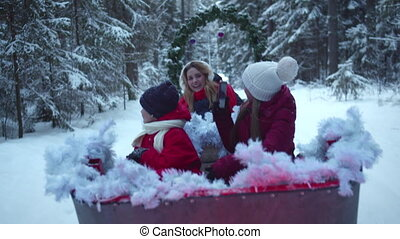 Family sledding and taking pictures on cell phone