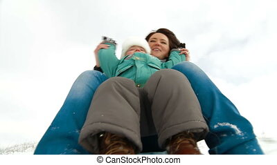 family sledding downhill