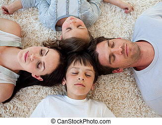 Family sleeping on the floor with heads together