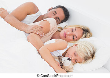 Family sleeping together on a same bed