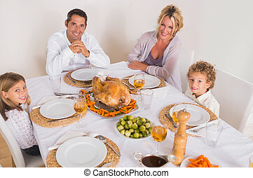 Family smiling around a roast dinner