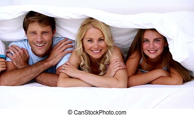 Family smiling at camera under the covers at home in bed