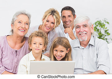 Family smiling in front of a laptop screen