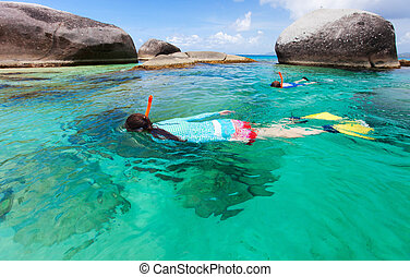 Family of young mother and son snorkeling in turquoise tropical water among huge granite