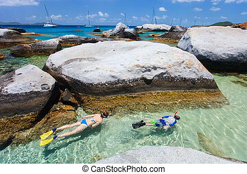 Family of young mother and son snorkeling in turquoise tropical water among huge granite boulders at The Baths beach area major tourist attraction on Virgin Gorda, British Virgin Islands, Caribbean