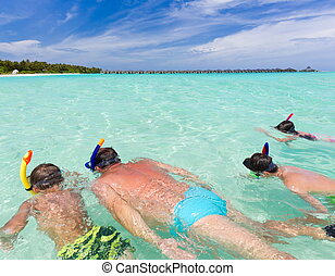 Family snorkeling in sea - Father snorkeling in tropical sea...