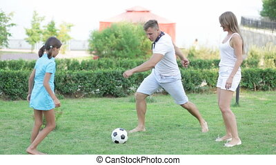 Active family playing soccer on the lawn