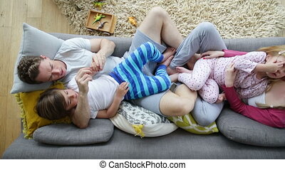 Family Sofa Cuddles - Family of four are enjoying some...