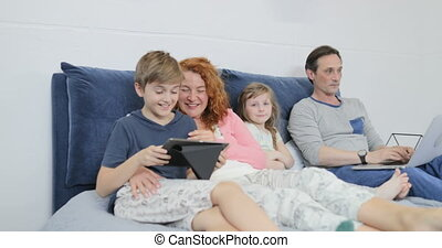 Family Spend Morning Together On Bed Parents With Children Using Tablet And Laptop Computer In Bedroom