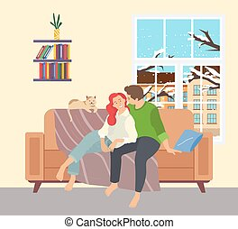 Family spending time in winter at home. Two loving people are sitting on the sofa with a fluffy cat