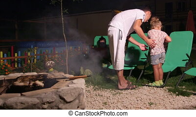 Family spending weekend in backyard near stone fire pit father grilling barbecue