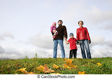 family stand on meadow at autumn