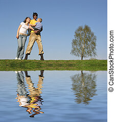 family stand with son. spring.water