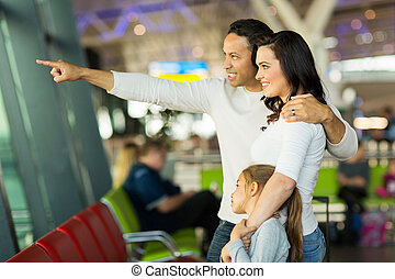 family standing at airport pointing outside