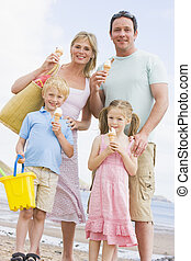 Family standing at beach with ice cream smiling