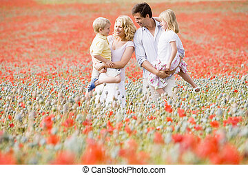 Family standing in poppy field smiling