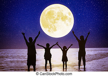 family standing on beach and watching the moon. Celebrate Mid autumn festival together