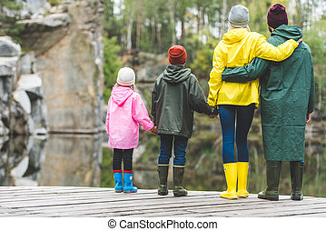 family standing on wooden bridge