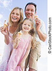 Family standing outdoors with ice cream smiling