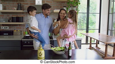 Family standing together at table in kitchen at home 4k