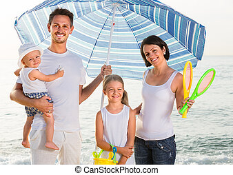 family standing under sun umbrella - positive family of four...
