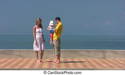 family stands against sea