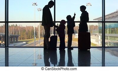 family stands against window at airport