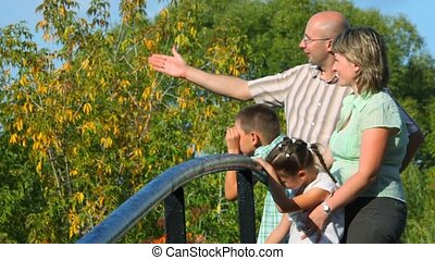 family stands on bridge in park and looks away