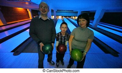 family stay with balls and show them in bowling club