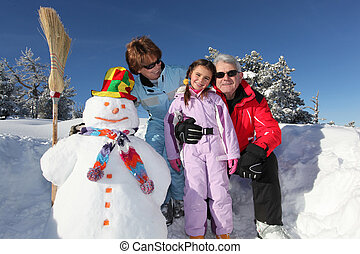 Family stood by snowman